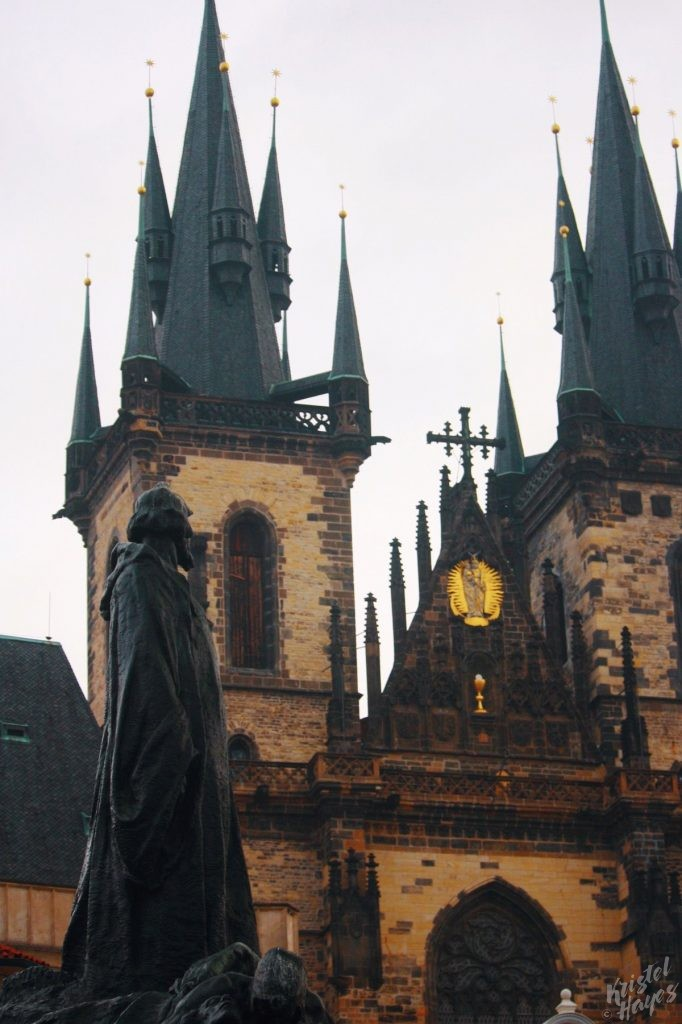 Statue in Old Town Square with Church of Our Lady before Týn
